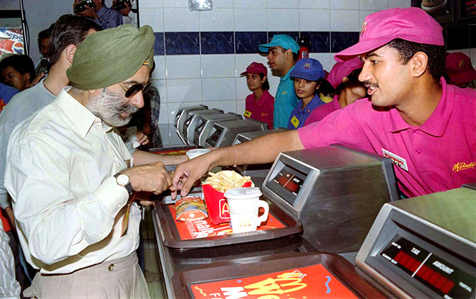 An Indian buys food from the first outlet in India of US fast food giant Mcdonald's in New Delhi, October 13, 1996. Photo: Stringer/Reuters