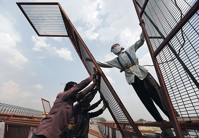 Workers install a metal fencing on a flyover to prevent people from throwing waste into the Yamuna river in New Delhi, April 7, 2016. Photograph: Anindito Mukherjee/Reuters