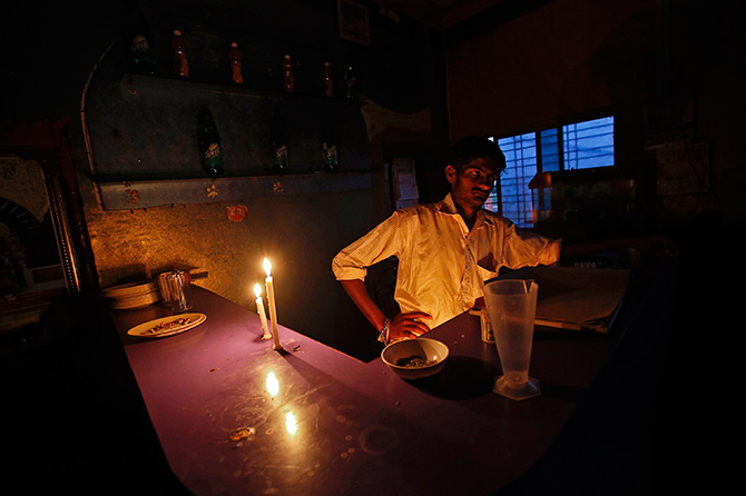 A man waits to serve customers by candle light in a country liquor bar with no electricity supply along the Nashik-Mumbai highway, about 150 km (93 miles) northwest of Mumbai, January 28, 2013. Photo: Vivek Prakash/Reuters