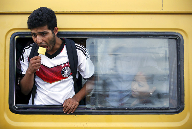 A passenger eats an ice-cream as he travels on the overcrowded bus in Nepal. Photo representational. Photo: Navesh Chitrakar/Reuters