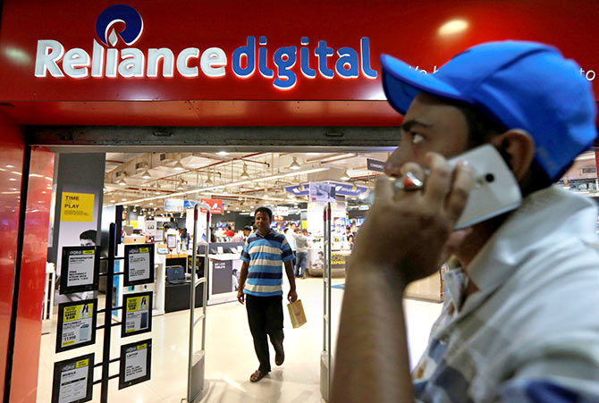 A man speaks on his mobile phone as he moves past a store of Reliance Industries Ltd, controlled by Mukesh Ambani, one of India's richest men, at a shopping mall on the outskirts of Kolkata, India, September 7, 2016. Picture taken September 7, 2016. Photo: Rupak De Chowdhuri/Reuters