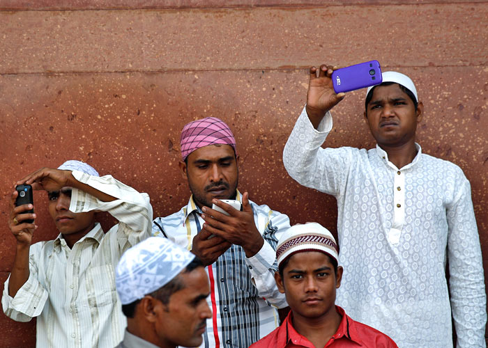 Muslims use their mobile phones after offering Eid al-Adha prayers at the Jama Masjid (Grand Mosque) in the old quarters of Delhi October 6, 2014. Ahmad Masood/Reuters