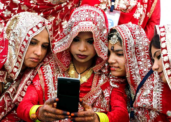 Muslim brides pose for a selfie as they wait for the start of a mass marriage ceremony in Ahmedabad, India, February 7, 2016. Amit Dave/Reuters