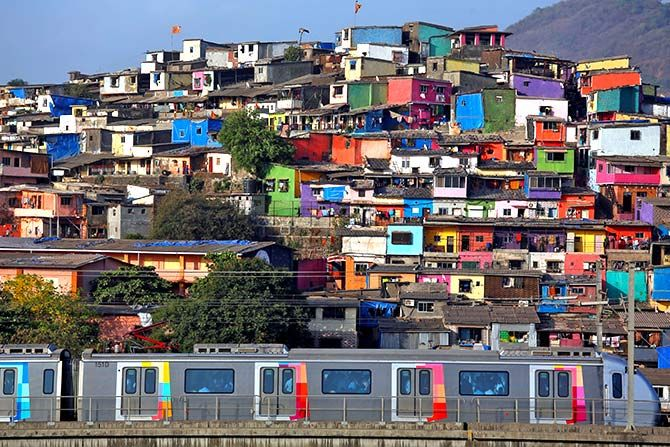 A metro train moves past a cluster of houses at the Asalpha slum in Mumbai, April 12, 2018. Photograph: Francis Mascarenhas/Reuters.