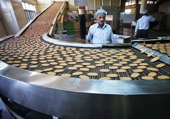 Biscuits on a conveyor belt after being baked at the Britannia factory in New Delhi. Photograph: Adnan Abidi/Reuters.