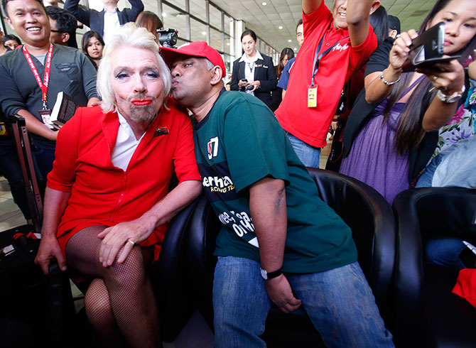 AirAsia's Chief Executive Tony Fernandes pretends to kiss British entrepreneur Richard Branson, left, who wears an AirAsia stewardess uniform, during an AirAsia promotional event in Sepang, outside Kuala Lumpur. Photograph: Bazuki Muhammad/Reuters