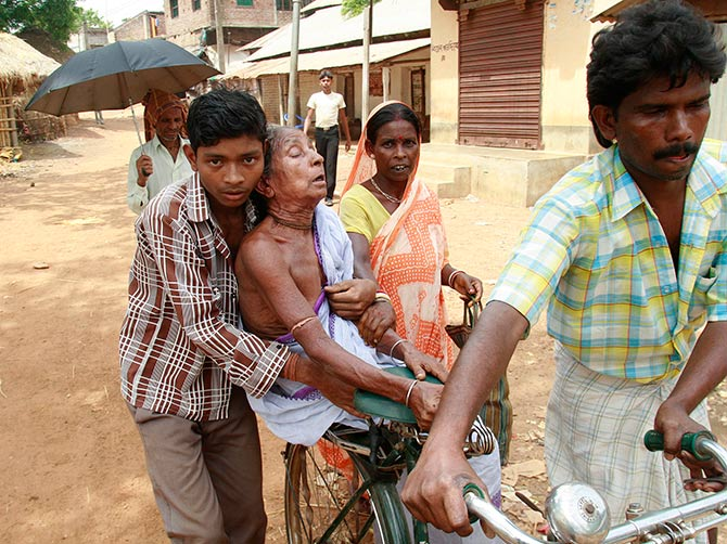 A woman being transported to the hospital at Lalgarh, West Midnapore district, some 170 km west of Kolkata. Photograph: Jayanta Shaw/Reuters.