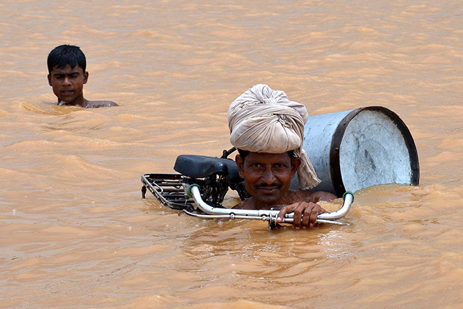 Still riding using a cycle during a flood at Maner, Patna district, Bihar. Photograph: Krishna Murari Kishan/Reuters.