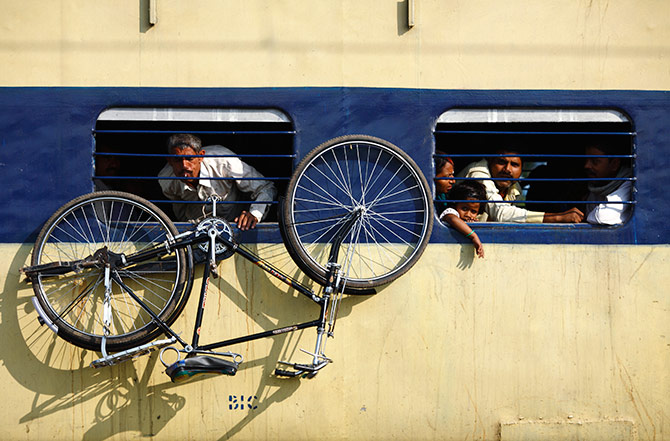 A bicycle hangs from the window of a train at Parsha Bazar railway station, Patna, Bihar. Photograph: Navesh Chitrakar/Reuters.