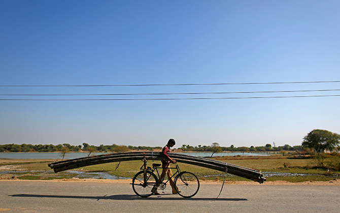 A farmer carries plastic pipes used for watering fields on his bicycle in Tonk, Rajasthan. Photograph: Danish Siddiqui/Reuters.