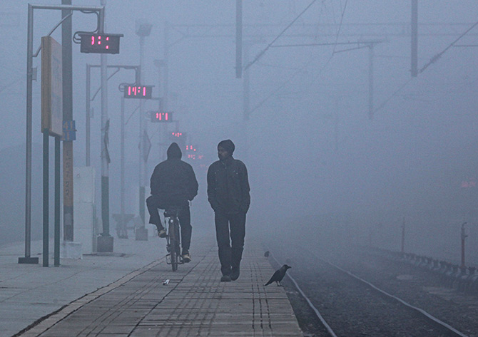 On a railway platform on a foggy winter morning in Chandigarh. Photograph: Ajay Verma/Reuters.