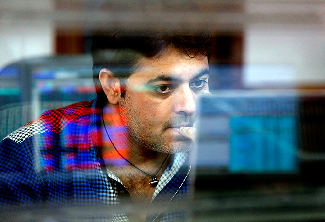 A broker reacts while trading at his computer terminal at a stock brokerage firm in Mumbai, India, February 26, 2016. Indian bonds, shares and the rupee gained on Friday after a key government report on the economy was seen as calling for fiscal prudence and stable inflation, while also acknowledging risks to the growth outlook. Photograph: Shailesh Andrade/Reuters.