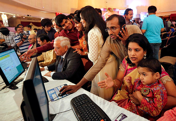 "A stockbroker trades as his family watches during the Diwali special trading session celebrating the annual Hindu festival of lights at the Bombay Stock Exchange (BSE) in Mumbai October 23, 2014. Indian shares rose in a special ""muhurat"" trading session for Diwali on Thursday, led by gains in Suzlon Energy Ltd. while hopes for continued foreign fund inflows into the country also boosted sentiment. Photograph: Shailesh Andrade/Reuters."