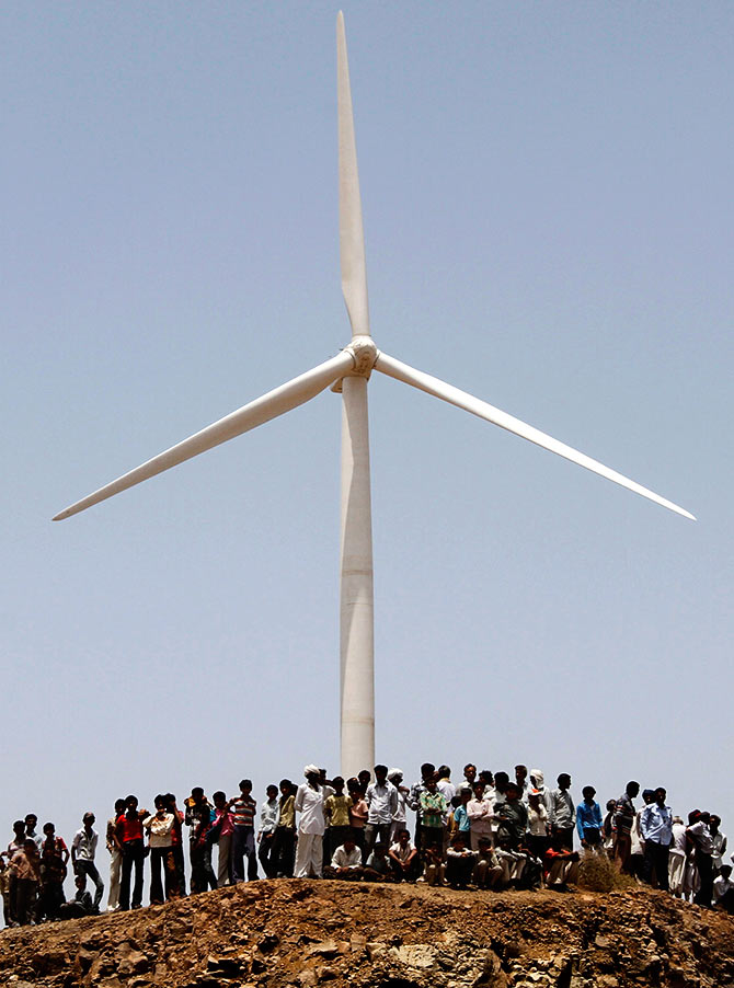Villagers stand under a power generating windmill turbine during the inauguration ceremony of the new 25 MW ReNew Power wind farm at Kalasar village in the western Indian state of Gujarat. Photograph: Amit Dave/Reuters