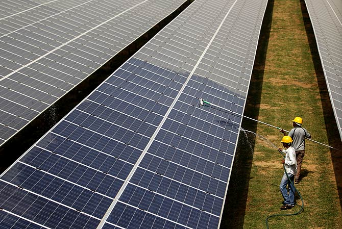 Workers clean photovoltaic panels inside a solar power plant in Gujarat, India, in this July 2, 2015. Photograph: Amit Dave/Reuters.