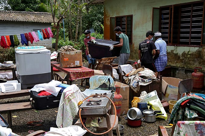Volunteers collect household items in the lawns of a residential house before cleaning the house following floods in the Kuttanad. Photograph: Sivaram V/Reuters.