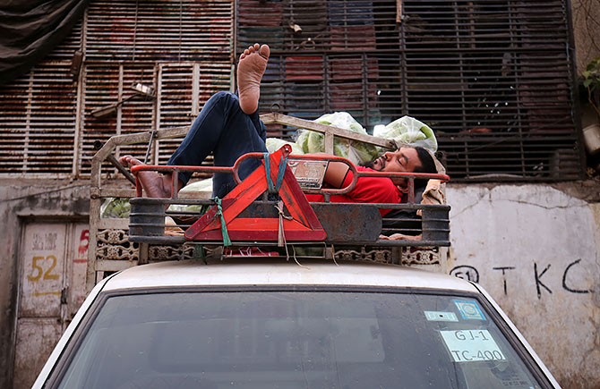 Snoozing aboard a mini truck in Ahmedabad. Photograph: Amit Dave/Reuters