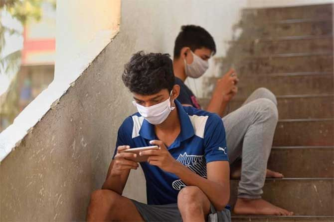 Young men play games on their mobile phones