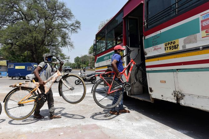Migrant labour take their bicycles inside a bus as they board it for their native places during the COVID-19 Photograph: ANI Photo
