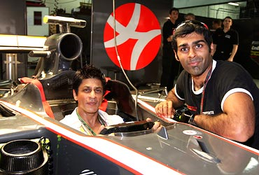 Shah Rukh Khan poses with HRT Formula One driver Karun Chandhok of India in the pits