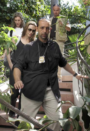 Angelina Jolie is escorted by security personnel as she leaves the Plaza hotel in Port-au-Prince