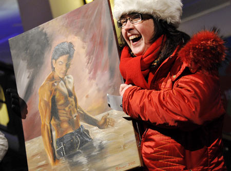 A fan holds a painting of SRK