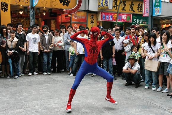A man dressed as Spider-Man dances to promote a Spider-Man film