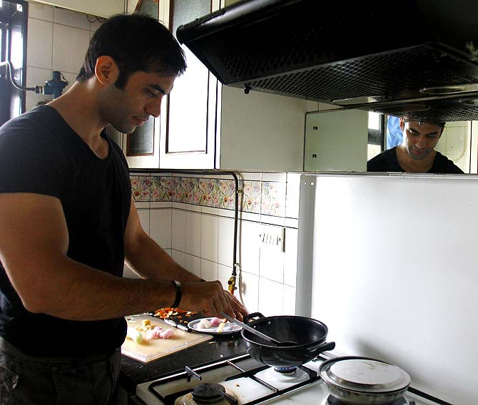 Kushal Punjabi cooking in his kitchen
