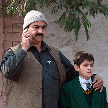 A man talks on a phone, with his arm around a student, outside a military run school that is under attack by Taliban gunmen in Peshawar