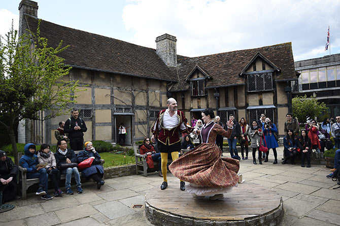 Tourists watch actors perform at the house where William Shakespeare was born during celebrations to mark the 400th anniversary of the playwright's death in Stratford-Upon-Avon.