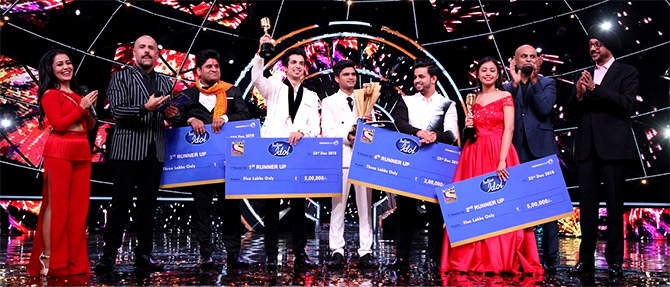 The top five finalists of Indian Idol, Season 10, with hosts Neha Kakkar and Vishal Dadlani, left and second from left, and others