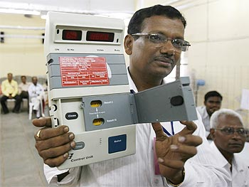 An officer holds a mock electronic voting machine as he explains the counting procedure to staff