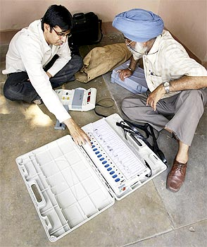 Polling officers check an EVM at a distribution centre