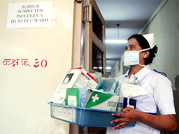 A nurse carries masks and medicine outside the influenza A (H1N1) ward in Mumbai