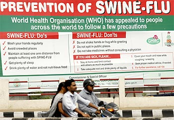 People ride past a billboard carrying messages on prevention of the Influenza A (H1N1) virus in Hyderabad