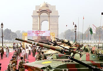Soldiers stand beside their displayed tanks at the India Gate in New Delhi