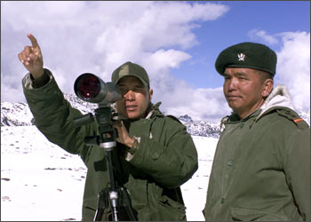 An Indian soldier points towards the border with China in Tawang