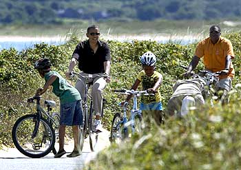 Obama rides a bike with his daughter Sasha (Centre) in Aquinnah on Martha's Vineyard