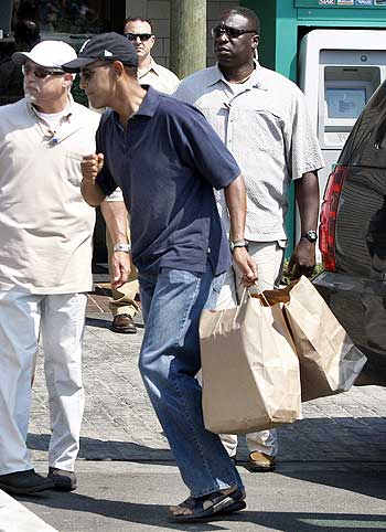Obama carries two bags containing takeout food that he bought from Nancy's restaurant in Oak Bluffs, Martha's Vineyard