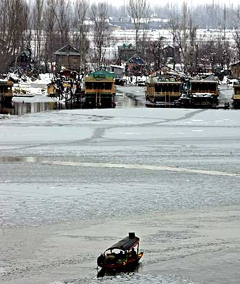 Kashmiris sit on a boat in the partially frozen Dal Lake in Srinagar