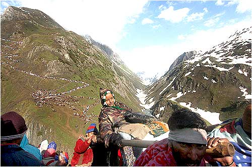 Porters carry an old woman to the shrine even as thousands follow behind