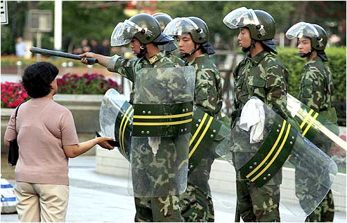 Chinese soldiers tell a woman to move on as they enforce a curfew in Urumqi
