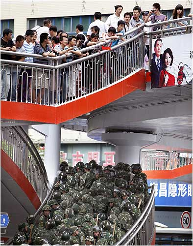 Chinese soldiers try to disperse a gathering of Han Chinese people in Urumqi