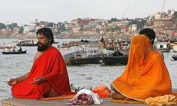 Holy men pray on the banks of river Ganges during the start of a solar eclipse in Varanasi, Uttar Pradesh