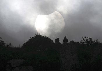 Local residents watch a solar eclipse on the peak of Malu Mountain in Liuzhou, China