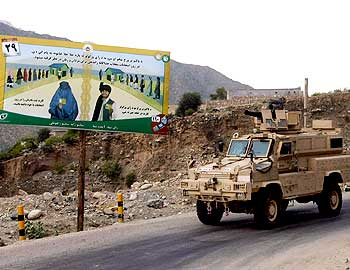 An armoured vehicle of the US army drives past an election sign in the valley of Kunar River in Afghanistan's Kunar province.