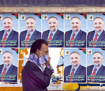 A man covers his face during a sandstorm while he walks past election posters of Mirwais Yasini, a presidential candidate, in Kabul.