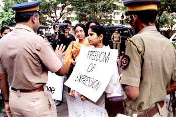 Police confront a Husain supporter at a demonstration outside the painter's Mumbai home