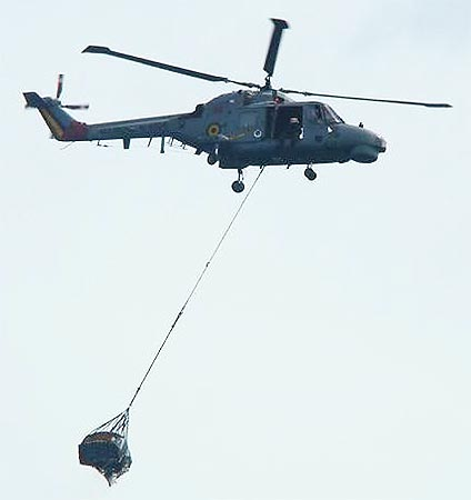 A helicopter transports to a ship a piece of debris.