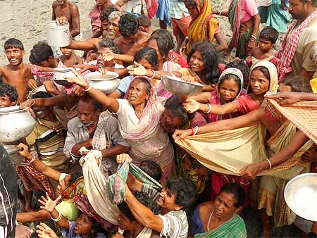 This rediff file photo shows Aila victims reach out for food and water as a relief boat reaches Bijoynagar in Gosaba, West Bengal.